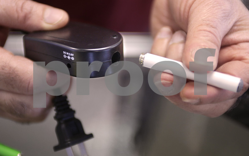 Kyle Bursaw – kbursaw@daily-chronicle.com<br /> <br /> Abraham Mustafa shows how the electronic cigarette charges—by screwing the front into a hole in the charger. Mustafa owns Smoker's World in DeKalb. <br /> <br /> 11.16.10