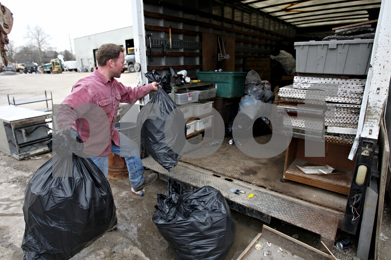 """Rob Winner – rwinner@daily-chronicle.com<br /> <br /> Eric Mathey places bags filled with aluminum cans into Terry Gustafson's trailer which is located at Mark's Machine Shop in Sycamore, Ill. on Wednesday March 24, 2010. Gustafson, known as Sycamore's """"can man,"""" has been unable to collect cans after being hospitalized."""