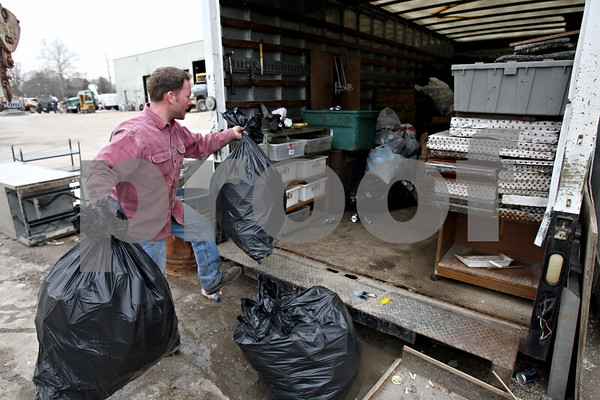 "Rob Winner – rwinner@daily-chronicle.com<br /> <br /> Eric Mathey places bags filled with aluminum cans into Terry Gustafson's trailer which is located at Mark's Machine Shop in Sycamore, Ill. on Wednesday March 24, 2010. Gustafson, known as Sycamore's ""can man,"" has been unable to collect cans after being hospitalized."