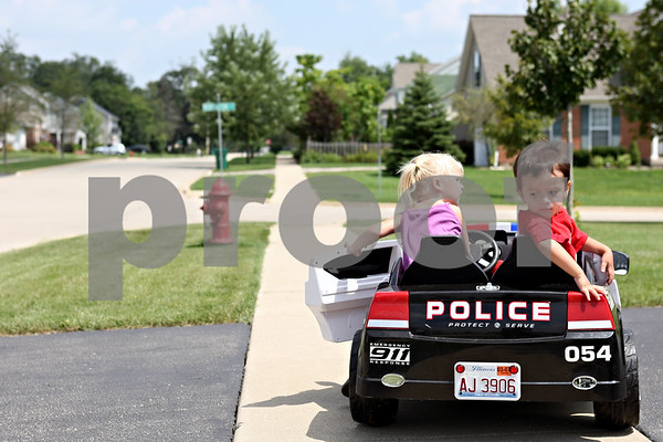 Rob Winner – rwinner@daily-chronicle.com<br /> <br /> DeKalb residents Lily Minalga, 2, and Luke Gal, 2, play with a battery powered toy vehicle on the sidewalk in front of Minalga's home near the intersection of Kensington Boulevard and Bush Street in Dekalb, Ill. on Friday August 6, 2010. Recently, a group of residents living in Kensington Pointe subdivision in DeKalb petitioned to have a traffic study done to make a four-way stop at the intersection.