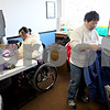 Rob Winner – rwinner@daily-chronicle.com<br /> Ashley Kim, 13, works on her homework while her mother, Jinhee, tends to the family's business in Genoa, Ill. on Thursday February 11, 2010. Ashley became paralyzed from the waist down after a swimming accident on September 12, 2009.
