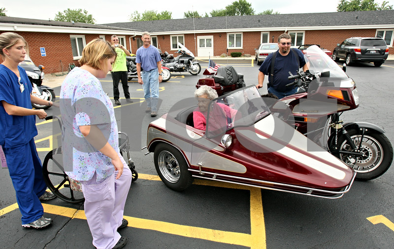 Rob Winner – rwinner@daily-chronicle.com<br /> <br /> One hundred two-year-old Clemmie Reed returns from her motorcycle ride with Gold Wing Road Riders Association of DeKalb member Brian Minick (right), of Waterman, during an ice cream social and bike show at the Shabbona Health Care Center in Shabbona, Ill. on Saturday July 31, 2010.