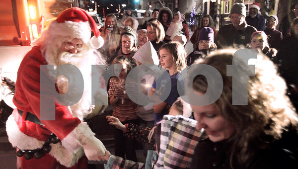 Kyle Bursaw – kbursaw@daily-chronicle.com<br /> <br /> Santa greets the crowd as he arrives just out side the Egyptian theatre on N. 2nd street in DeKalb, Ill. on Thursday, Dec. 2, 2010.