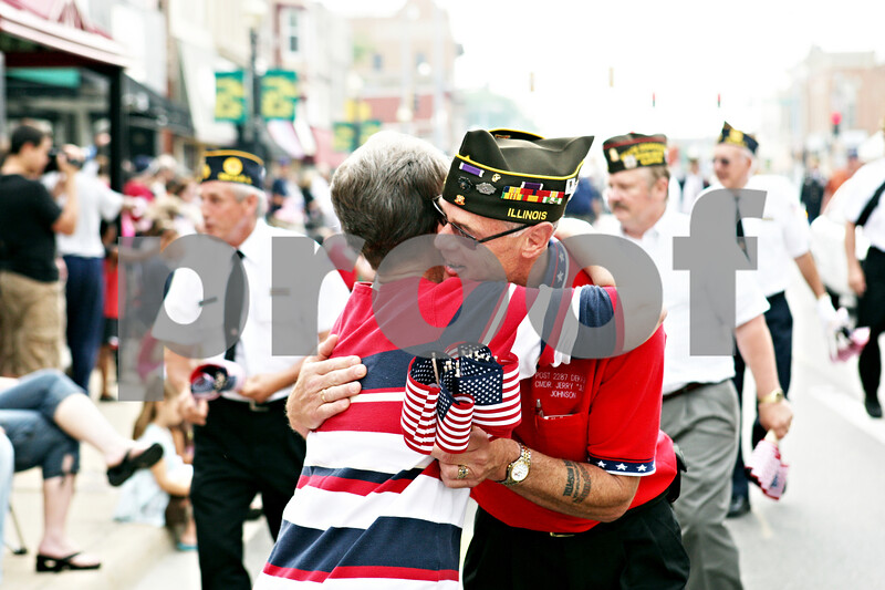 """Rob Winner – rwinner@daily-chronicle.com<br /> <br /> Commander Jerry """"Jug"""" Johnson, of VFW Post 2287, hugs his sister, Cherry Potts, while handing out flags during a Memorial Day parade heading west on Lincoln Highway on Monday May 31, 2010 in DeKalb, Ill."""