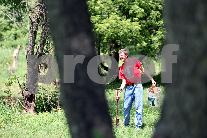 Rob Winner – rwinner@daily-chronicle.com<br /> <br /> Chris Gherity looks for an area to plant young oak trees on his property on Tuesday June 1, 2010 in Kingston, Ill. Gherity is a contractor with the Department of Natural Resources, growing trees for the DNR on his property.
