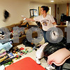 Rob Winner – rwinner@daily-chronicle.com<br /> Kelly Pedersen, of Time is Money, Inc., tosses an article of clothing into a pile while sorting items in the basement of a client's home in Sycamore, Ill. on Friday February 5, 2010.