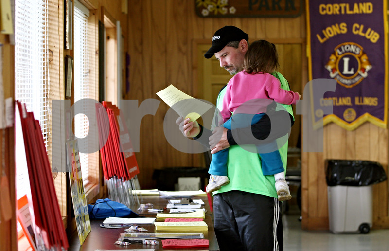 Rob Winner – rwinner@daily-chronicle.com<br /> <br /> Cortland resident Mike Wiseman looks over some literature about the effects of hydrogen sulfide while holding his 1-year-old daughter, Sophie, during a town hall meeting for those against the proposed landfill expansion in DeKalb county at the Cortland Lions Club in Cortland, Ill. on Saturday October 2, 2010.