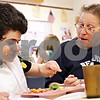 Beck Diefenbach  -  bdiefenbach@daily-chronicle.com<br /> <br /> Linda Maffei (right), of DeKalb, helps her daughter Chrissy Cowan (left) with her meal during the biweekly VAC community dinner at the Senior Services Center in DeKalb, Ill., on Wednesday March 31, 2010.