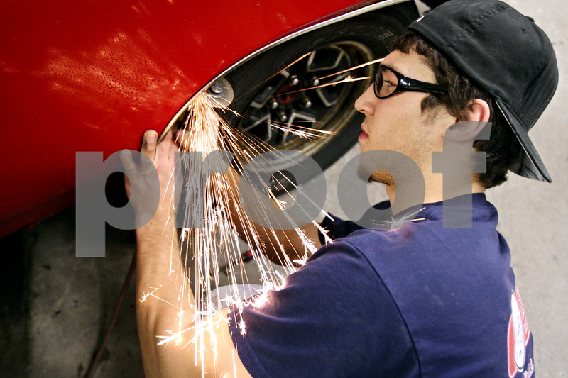 Rob Winner – rwinner@daily-chronicle.com<br /> <br /> Brandon Wagner of RPM Restorations uses an angle grinder to remove a wheel well molding from a 1970 Buick Skylark which is being restored for Jessica Koker of the United States Navy.