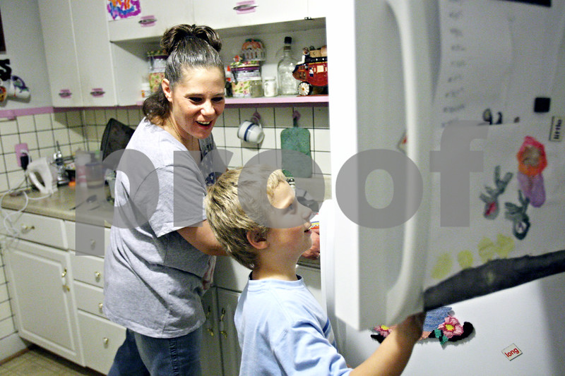 Rob Winner – rwinner@daily-chronicle.com<br /> <br /> Elizabeth Kopec questions her son Jimmy, 7, as he peers into the freezer looking for a popsicle before dinner at their Malta home on Wednesday. Kopec, a mother of two, has a LINK card which was not credited at the beginning of the month.