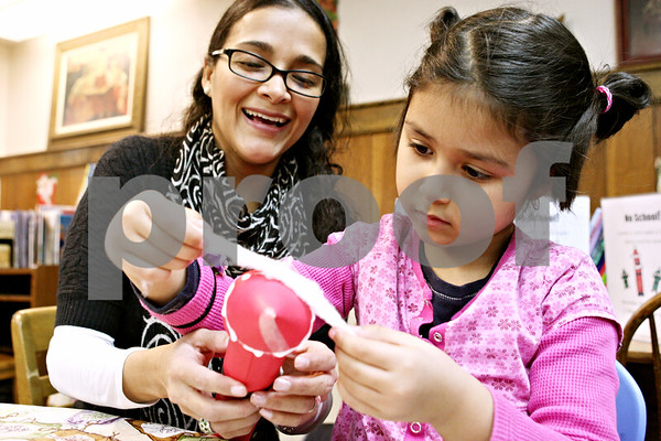 Rob Winner – rwinner@daily-chronicle.com<br /> <br /> DeKalb residents Lady Cohen and her daughter, Emma, 5, make Santa Claus during holiday craft time at the DeKalb Public Library on Monday afternoon.