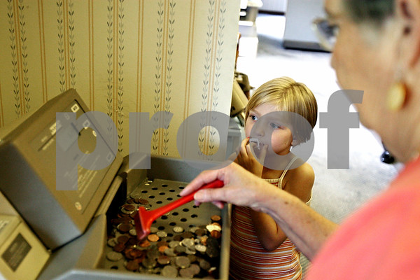 Rob Winner – rwinner@daily-chronicle.com<br /> <br /> 6-year-old Jayden Wogen, of DeKalb, watches as Resource Bank teller Dena Johnson counts her change with a machine on Tuesday August 10, 2010 in Malta, Ill.