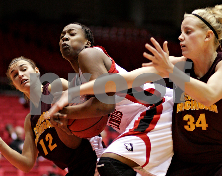 Beck Diefenbach  -  bdiefenbach@daily-chronicle.com<br /> <br /> Northern Illinois' Mauvolyene Adams (32, center) tries to keep the ball from Central Michigan's Britni Houghton (12, left) and Kaihla Szunko (34, right) during the first half of the game at the NIU Convocation Center in DeKalb, Ill., on Wednesday Jan. 20, 2010