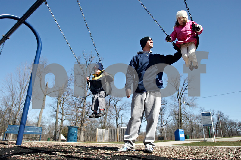 Rob Winner – rwinner@daily-chronicle.com<br /> <br /> Justin Kees (center), of Cortland, spends some time at the playground of Hopkins Park with his two children Jackson (left), 3, and Madeline, 6, on Friday March 26, 2010 in DeKalb, Ill.