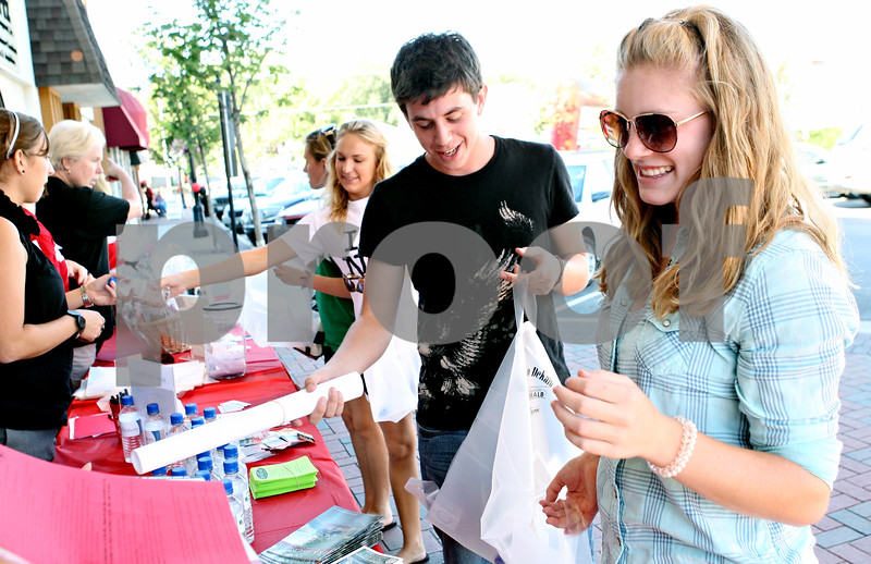 Rob Winner  -  rwinner@daily-chronicle.com<br /> <br /> Incoming Northern Illinois University freshmen Chase Zacher (left), of Long Grove, and Lauren Boddy, of Lily Lake, receive loads of freebies in front of the Egyptian Theatre while participating in Huskies SEE DeKalb event in downtown DeKalb, Ill. on Thursday August 26, 2010.