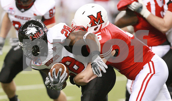 Kyle Bursaw – kbursaw@daily-chronicle.com<br /> <br /> Northern Illinois running back Chad Spann (28) fights for more yards as Miami (OH) linebacker Ryan Kennedy (5) brings him down during the first quarter of the MAC Championship game between the Northern Illinois Huskies game and the Miami (Ohio) Redhawks<br /> at Ford Field in Detroit, Mich. on Friday, Dec. 3, 2010.