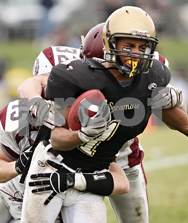 Beck Diefenbach  -  bdiefenbach@daily-chronicle.com<br /> <br /> Sycamore running back Marckie Hayes  (1) is tackled by Montini linebackers Ryan Gorrell (32) and Alex Walters (45) behind the line of scrimmage during the third quarter of the playoff game at Sycamore High School in Sycamore, Ill., on Saturday Nov. 14, 2009.