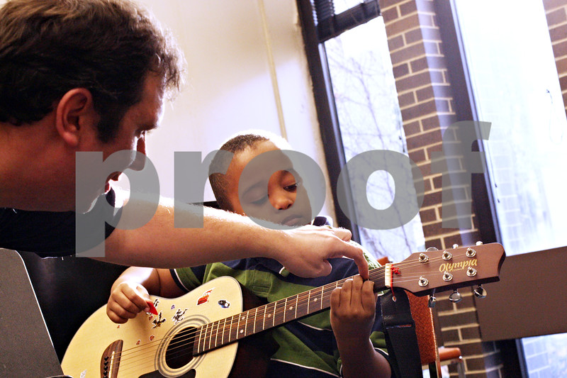 Beck Diefenbach  -  bdiefenbach@daily-chronicle.com<br /> <br /> Teacher Quentin Dover (left) helps Nicholas Chen, 8, of DeKalb, Ill., with his finger placement during a guitar basics lesson at the Northern Illinois University Community School of Music in DeKalb, Ill., on Wednesday March 17, 2010.