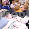 Kyle Bursaw – kbursaw@daily-chronicle.com<br /> <br /> Jean Baker reaches into a pile of donated clothes waiting to be sorted and priced. Baker and co-worker Denise Soto, background, both sort and price clothing in the back of Goodwill in DeKalb, Ill. on Wednesday, Dec. 15, 2010.