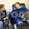 Beck Diefenbach  -  bdiefenbach@daily-chronicle.com<br /> <br /> Northern Illinois University students Michelle Mutch, left, holds the hand of her boyfriend Philip Moe as he donates bone marrow at Rock River Valley Blood Center in Rockford, Ill., on Thursday Feb. 18, 2010. Last April, Moe registered with the National Bone Marrow Donor Registry at NIU and was found to be a match with a needy patient.