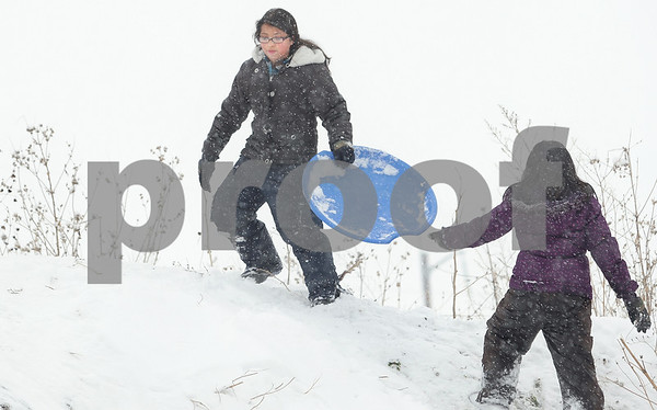 Kyle Bursaw – kbursaw@daily-chronicle.com<br /> <br /> Sisters Cecilia, left, and Lorena Robles climb a hill to sled down it again in their neighborhood in DeKalb, Ill. on Friday, Dec. 24, 2010.