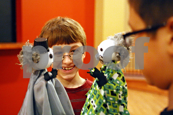 Rob Winner – rwinner@daily-chronicle.com<br /> Brandon Lovell (center), 11, and Tommy Phetmeuangmay, 11, play with two hand puppets that they created at a puppet making workshop at StageCoach Players in DeKalb, Ill. on Saturday February 13, 2010.