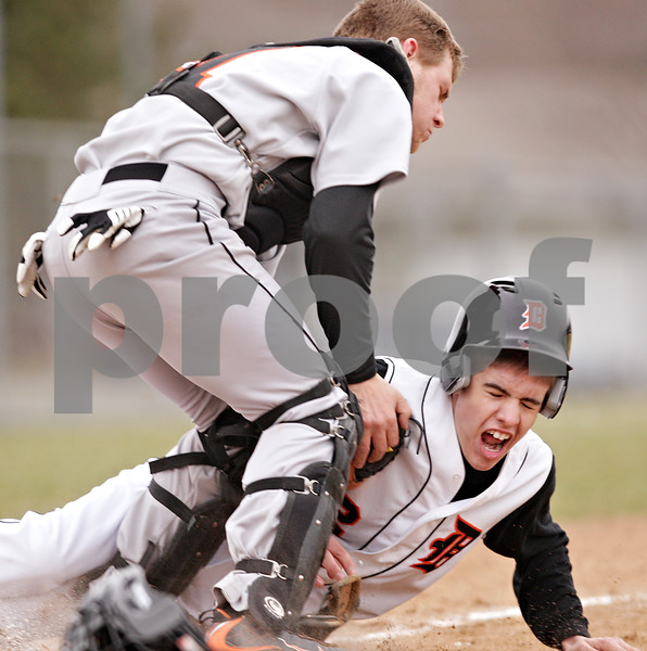Beck Diefenbach  -  bdiefenbach@daily-chronicle.com<br /> <br /> DeKalb's Nate Diedrich (2, bottom) tries to steal home but is tagged out by Sandwich catcher Mike Considine during the bottom of the fourth inning of the game at DeKalb High School in DeKalb, Ill., on Wednesday March 24, 2010. DeKalb defeated Sandwich 7 to 1.