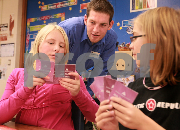 Kyle Bursaw – kbursaw@daily-chronicle.com<br /> <br /> Patrick Bannon, a senior in business administration at NIU, helps Camryn Anderson, left, and Kate Majerus, right, with a card game about different career fields. Bannon volunteered with Junior Achievement and taught lessons to fifth-graders at North Elementary in Sycamore, Ill. on Nov. 12, 2010.