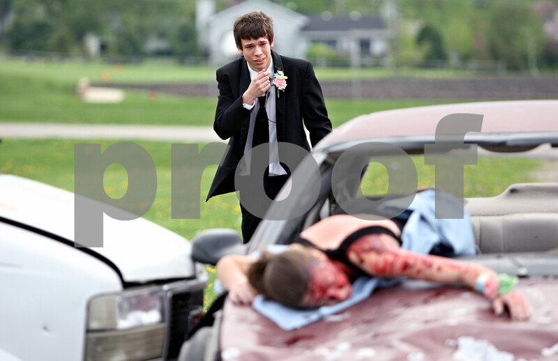 Rob Winner –  rwinner@daily-chronicle.com<br /> <br /> During a simulation, Clayton Peterson (back) looks at the wreckage of a two vehicle collision as Erica Arends lays on the hood of one of the vehicles at Indian Creek High School in Shabbona, Ill. on Friday April 30, 2010.