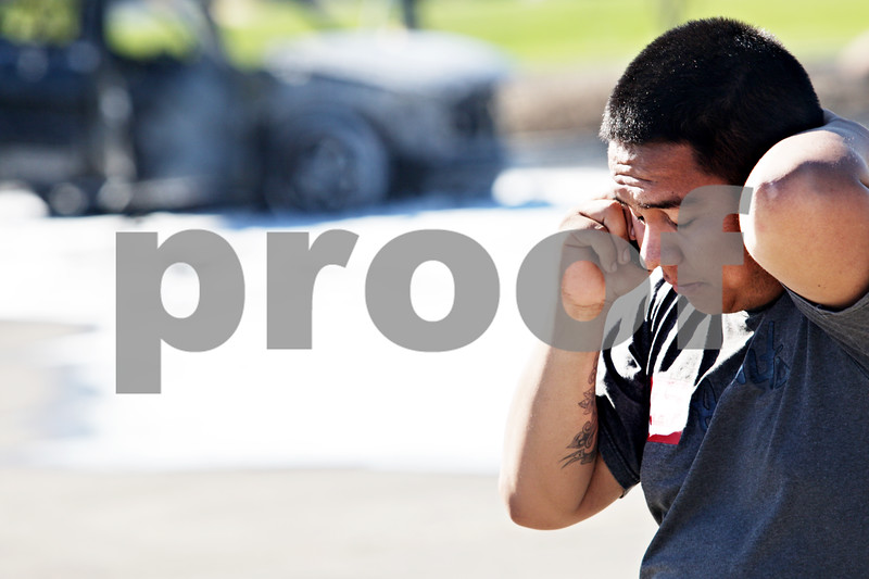 Beck Diefenbach  -  bdiefenbach@daily-chronicle.com<br /> <br /> Angel Garcia, of DeKalb, talks on the phone after his Lincoln Aviator was destroyed in a car fire in the Walmart parking lot in DeKalb, Ill., on Friday July 2, 2010.