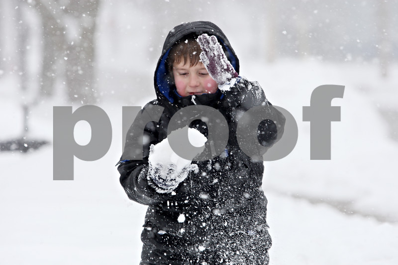 Rob Winner – rwinner@daily-chronicle.com<br /> C.J. Germain, 7, packs together snow during a snowball fight with his brother, Andy (not pictured), as the two played in front of their home in DeKalb, Ill. on Tuesday February 9, 2010.