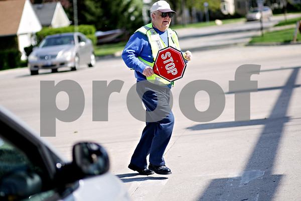 Beck Diefenbach  -  bdiefenbach@daily-chronicle.com<br /> <br /> Sycamore crossing guard Jack Knudson rushes out of the intersection after stopping traffic for students at Sycamore High School in Sycamore, Ill., on Thursday April 29, 2010.