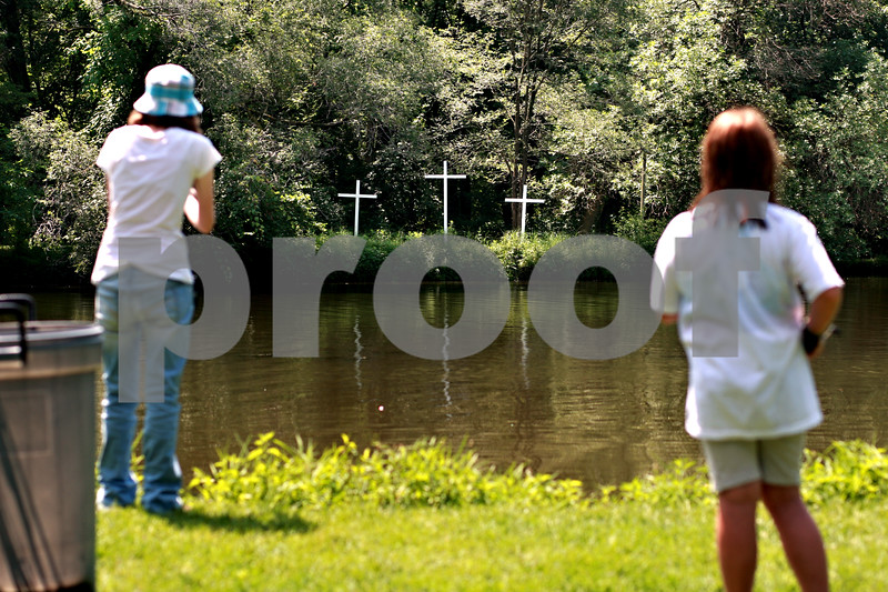 Beck Diefenbach  -  bdiefenbach@daily-chronicle.com<br /> <br /> Three crosses stand on the opposite side of the lake as campers fish at Walcamp Outdoor Ministries in Kingston, Ill., on Monday July 12, 2010.