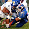 Beck Diefenbach  -  bdiefenbach@daily-chronicle.com<br /> <br /> Aurora Central Catholic running back Luis Hizo (2, left) is tackled by Genoa-Kington lineback Robert Thurlby (24) during the first quarter of the game at Genoa-Kingston High school in Genoa, Ill., on Friday Aug. 27, 2010.