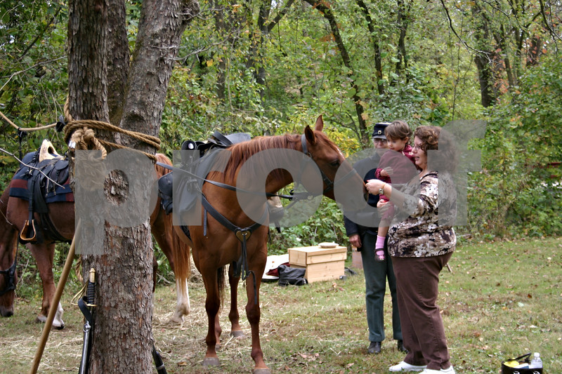 Dana Herra dherra@daily-chronicle.com<br /> <br /> Dee Stroud and her 2-year-old daughter, Katie, pet a horse Sunday while Civil War re-enactor Bev Mansfield looks on. A Civil War encampment was one of many activities featured at the Walcamp Fall Festival in Kingston.