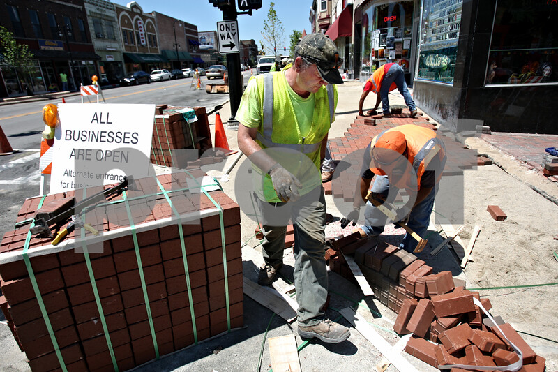 Rob Winner – rwinner@daily-chronicle.com<br /> <br /> Workers lay bricks on the sidewalks as construction on Lincoln Highway in DeKalb, Ill. begins to wrap up on Friday July 16, 2010.