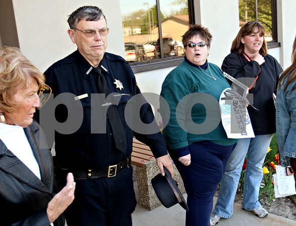 Beck Diefenbach  -  bdiefenbach@daily-chronicle.com<br /> <br /> Lisa Wilcox (second from right), of DeKalb. voices her disapproval of Pollution Control Facility Committee member Marlene Allen (far left) as she exits with Sheriff Roger Scott, second from left, following the board's approval of the landfill expansion at the Legislative Center in Sycamore, Ill., on Tuesday April 27, 2010.