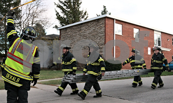 Kyle Bursaw - kbursaw@daily-chronicle.com<br /> <br /> Firefighters carry a ladder back to their truck after looking at the top of 916 Greenbrier Rd, where the roof was blown off.