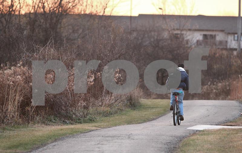 Kyle Bursaw – kbursaw@daily-chronicle.com<br /> <br /> A bicyclist rides down the path at Prairie Park in DeKalb, Ill. on Nov. 16, 2010.