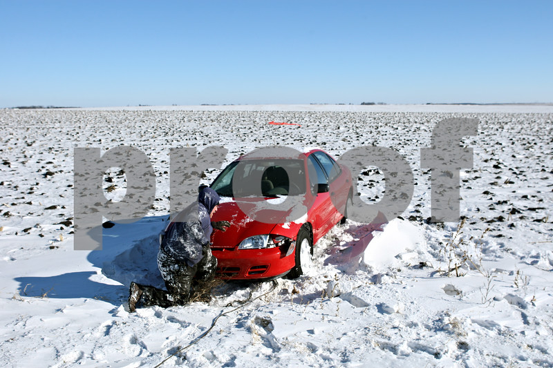 Rob Winner – rwinner@daily-chronicle.com<br /> <br /> On Monday afternoon, John Sturgill of GreenCo Towing in Yorkville attaches a tow cable to the front of a vehicle stuck in a field off of Somonauk Road in Squaw Grove Township.