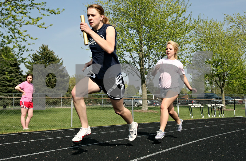 Rob Winner – rwinner@daily-chronicle.com<br /> <br /> Members of the girls track including Krystan Scheffler (front) and Taylor Madeley work on handing off the baton during practice in Sycamore, Ill. on Thursday April 22, 2010.