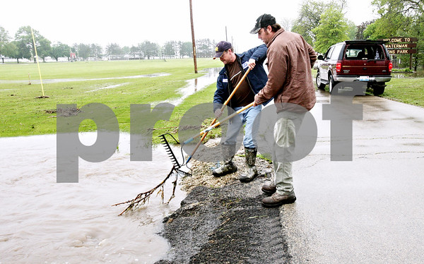 Rob Winner – rwinner@daily-chronicle.com<br /> <br /> Dave Martin (left) and Michael Boesche use rakes to clear debris to keep the water flowing within a drainage ditch near Lions Park in Waterman, Ill. on Thursday May 13, 2010.