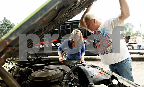 Rob Winner – rwinner@daily-chronicle.com<br /> <br /> Powder puff race car driver Danielle Heath, of Rolling Meadows, and her father John Heath, of Kingston, look under the hood of Danielle's 1986 Chevrolet Caprice at Sycamore Speedway in Maple Park, Ill. on Friday July 30, 2010.