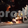 Beck Diefenbach  -  bdiefenbach@daily-chronicle.com<br /> <br /> A member of the Northern Illinois community lays a candle by the five crosses representing the victims of the shootings following the candlelight vigil at the Martin Luther King Commons on the campus of NIU in DeKalb, Ill., on Sunday Feb. 14, 2010.