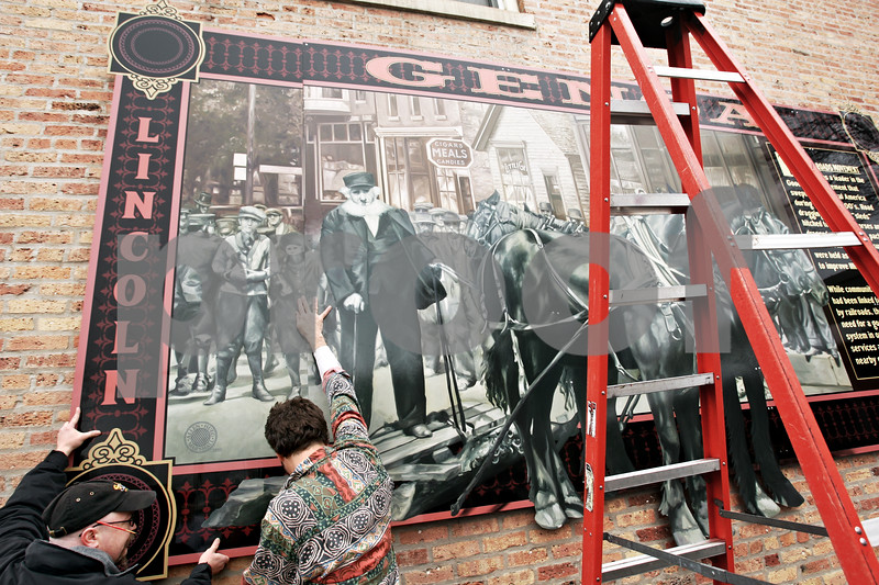 "Beck Diefenbach - bdiefenbach@daily-chronicle.com<br /> <br /> Joe Marshall (far left) and Jay Allen, of Shaw Craft Sign Company, installs the last panel of a mural on the exterior of the Genoa Public Library in Genoa, Ill., on Monday March 8, 2010. The mural recognized Genoa's role in the ""Good Roads Movement."""