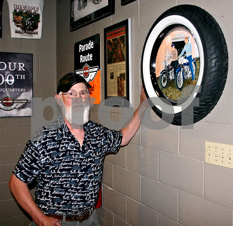 Lauren Stott - lstott@daily-chronicle.com<br /> <br /> Lynden Bute poses near artwork he painted to comemmorate the lives of two friends, Wayne Pierce, Sr. and Wayne Pierce, Jr. at Pierce Harley-Davidson, 969 Peace Road.