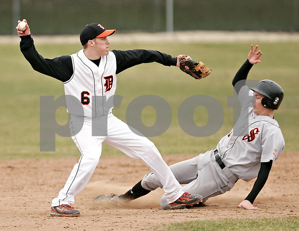 Beck Diefenbach  -  bdiefenbach@daily-chronicle.com<br /> <br /> DeKalb second baseman Kevin Sullivan (6, left) throws to first base after getting Sandwich's Justin Wegener (8) out at second base during the top of the fourth inning of the game at DeKalb High School in DeKalb, Ill., on Wednesday March 24, 2010. DeKalb defeated Sandwich 7 to 1.