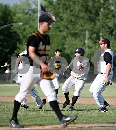 Rob Winner – rwinner@daily-chronicle.com<br /> <br /> Sycamore pitcher Nathan Harbecke (front) leaves the field as DeKalb's Jake Gordon (10) begins celebrating with his teammates after knocking in the winning run in the bottom of the seventh inning during the IHSA Class 3A DeKalb Sectional semifinal on Wednesday June 2, 2010 in DeKalb, Ill.