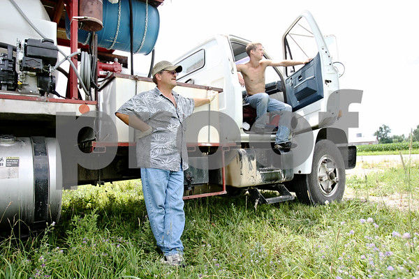 Rob Winner – rwinner@daily-chronicle.com<br /> <br /> William Henley (left) and Mitchell Hendrickson, of Hendrickson Flying Service located in Rochelle, wait in the shade of their truck as helicopter pilot Ron Smith (not pictured) sprays farm fields with fungicide near Fenstermaker and Barber Greene roads in Cortland Township on Friday July 23, 2010.