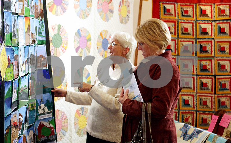 Rob Winner – rwinner@daily-chronicle.com<br /> <br /> At the Kirkland Historical Society Quilt Show at United Methodist Church in Kirkland, Ill. on Saturday March 20, 2010, Joanne Fruit (left) and her daughter Brooke Fruit look at a quilt that was created by Hiawatha art students.